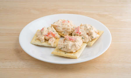atop: A plate of saltine crackers with lobster snack dip atop a wood table top.