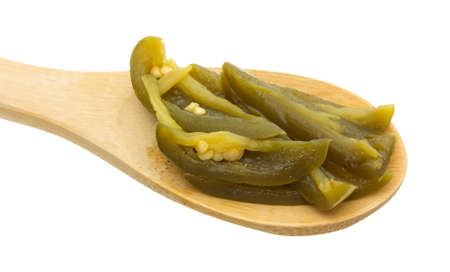 A portion of sliced jalapeno peppers upon a wood kitchen spoon on a white background.