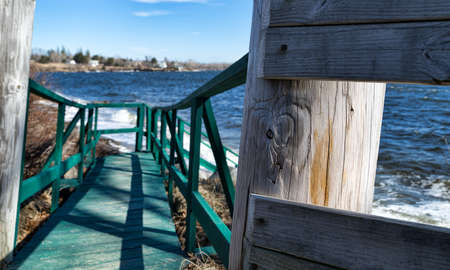 high tide: An old green painted walkway leading to a gravel beach at high tide with storm surf on Penobscot bay in Searsport, Maine in the springtime.