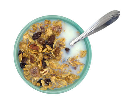 skim: Top view of a bowl of pecans, raisins and dates breakfast cereal with skim milk plus spoon isolated on a white background.