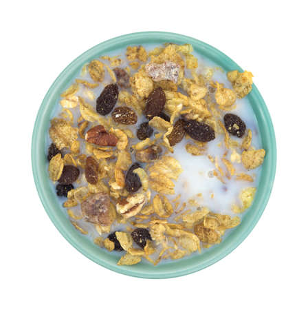 skim: Top view of a bowl of pecans, raisins and dates breakfast cereal with skim milk isolated on a white background. Stock Photo