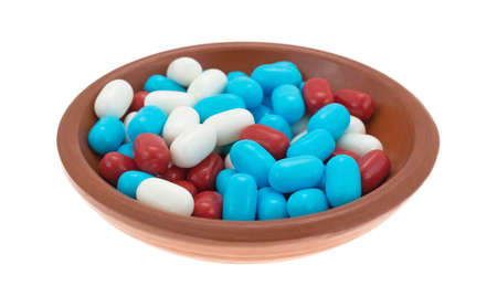 Side view of an assortment of red white and blue breath mints in a small bowl isolated on a white background. Stock fotó