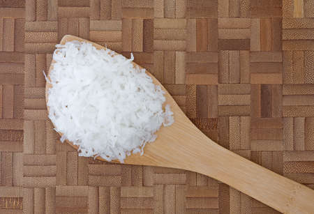 sweetened: Top view of a portion of sweetened coconut flakes on a spoon atop a wood cutting board.