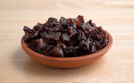 atop: A portion of diced prunes in a small bowl atop a wood table top.