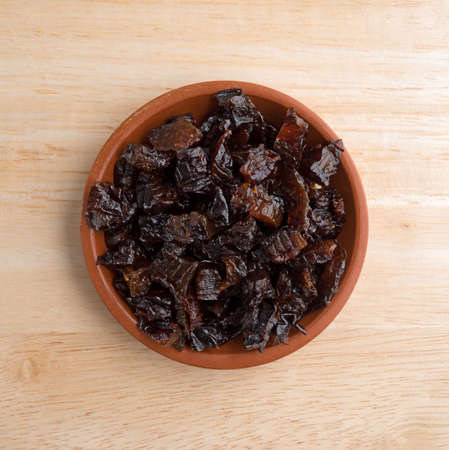 diced: Top view of a portion of diced prunes in a small bowl atop a wood table top. Stock Photo