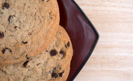 hypoallergenic: Top close view of two chocolate chip gluten-free cookies on a deep red plate atop a wood table top. Stock Photo