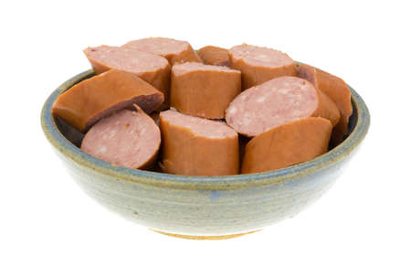 reduced: Several slices of reduced calorie kielbasa sausage in an old stoneware bowl isolated on a white background.