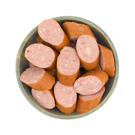 stoneware: Top view of several slices of reduced calorie kielbasa sausage in an old stoneware bowl isolated on a white background. Stock Photo