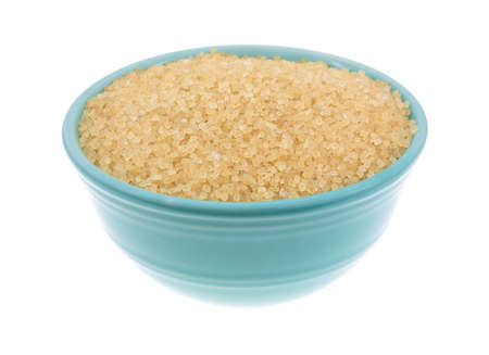 minimally: Side view of a bowl filled with turbinado sugar isolated on a white background. Stock Photo