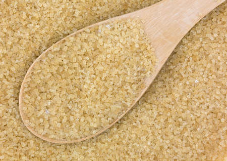 minimally: Close view of a spoonful of turbinado sugar atop more sugar.