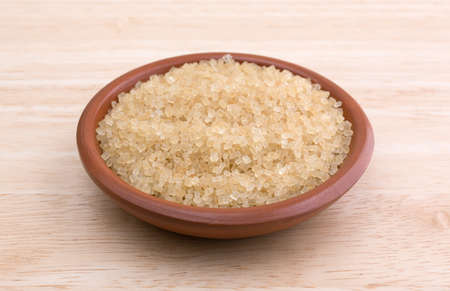 minimally: Side view of a portion of turbinado sugar in a small bowl atop a wood table top.