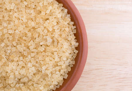 minimally: Top close view of a portion of turbinado sugar in a small bowl atop a wood table top. Stock Photo