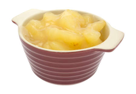 Side view of a bowl filled with apple pie filling isolated on a white background.