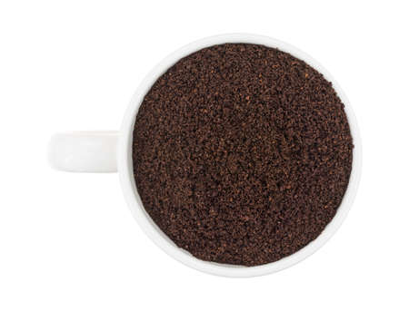kona: Top view of a cup filled with Kona ground beans coffee isolated on a white background.