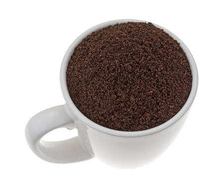 kona: A cup filled with Kona ground beans coffee isolated on a white background. Stock Photo