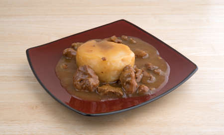 A serving of a mashed potatoes in gravy with beef tips TV dinner on a maroon plate atop a wood table top. Stock Photo