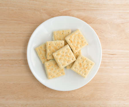 inexpensive: Top view of cream cheese and chives crackers on a white plate atop a wood table top. Stock Photo