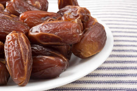 deglet: A close view of Tunisian pitted dates on a plate atop a striped table cloth.