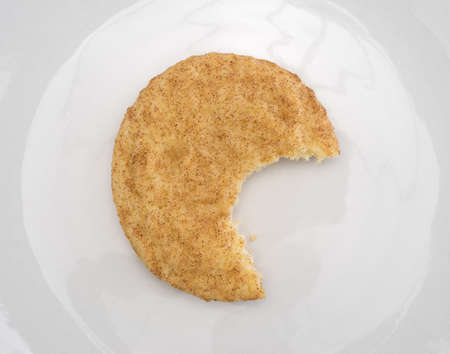 bitten: Top view of a bitten snickerdoodle cookie on an off white plate.