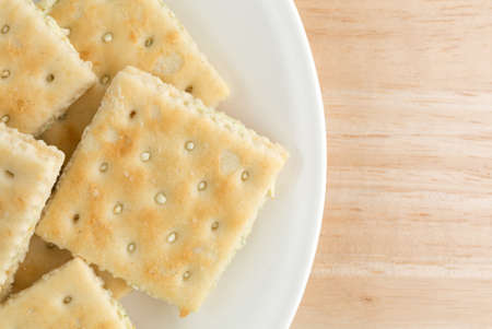 inexpensive: Top close view of cream cheese and chives crackers on a white plate atop a wood table top.