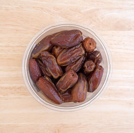 Top view of a container of Tunisian pitted dates a wood table top. Stock Photo