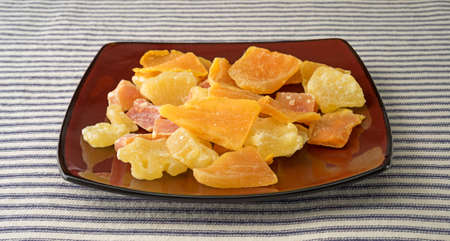 sugared: A plate with pineapple, mango and papaya sugared dried fruit on a striped tablecloth.