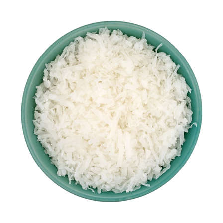 sweetened: Top view of sweetened coconut flakes filling a small bowl isolated on a white background.