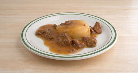 A meal of a mashed potatoes in gravy with beef tips TV dinner on a plate atop a wood table top. Stock Photo