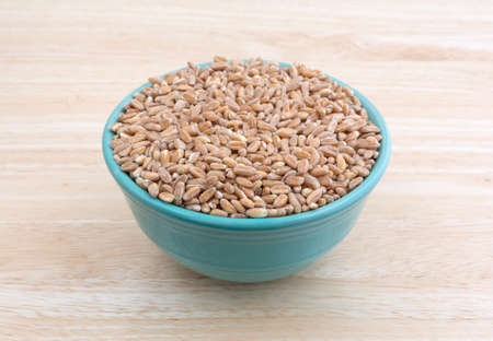 Side view of farrow organic grain filling a small bowl atop a wood table top.