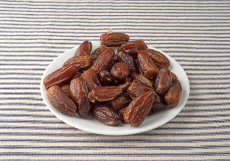 deglet: Tunisian pitted dates on a white plate atop a blue striped table cloth.
