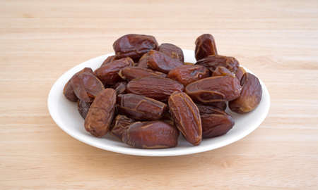 Side view of a plate of Tunisian pitted dates a wood table top.