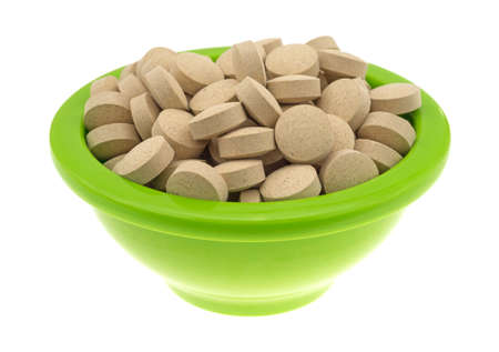 brewers: Side view of a green bowl filled with brewers yeast nutritional supplement tablets isolated on a white background.