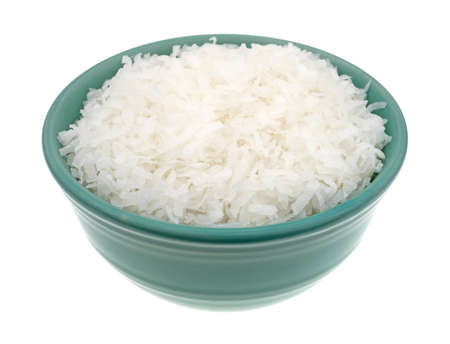 Side view of sweetened coconut flakes filling a small bowl isolated on a white background. Banco de Imagens