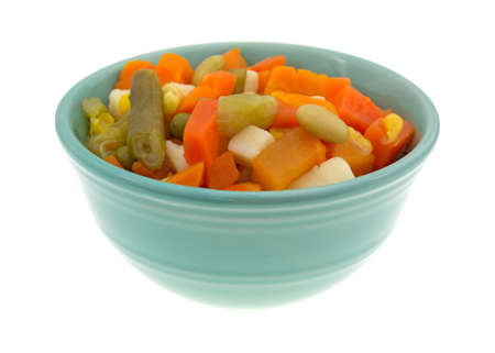mixed vegetables: Side view of a portion of mixed vegetables in a small bowl isolated on a white background.