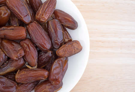 deglet: Top close view of a plate of Tunisian pitted dates a wood table top. Stock Photo