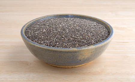 stoneware: An old stoneware bowl filled with organic chia seeds on a wood table top.