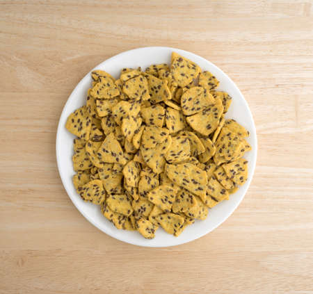 Top view of a portion of flax seed corn chips on a white plate atop a wood table top. Imagens