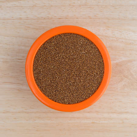 Top view of teff grain filling an orange bowl atop a wood table top.