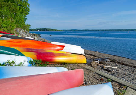 dinghies: View of several canoes, kayaks and dinghies stored on a beach at Northport Maine in the early morning light.