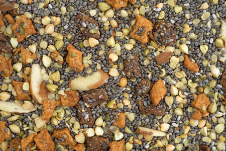 Very close view of dry breakfast cereal consisting of chia seeds, nuts, and dried fruit. Stock Photo