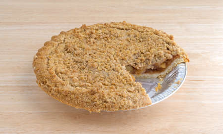 dutch: Side view of a Dutch apple pie in a tinfoil baking dish on a wood table top with one slice missing. Stock Photo