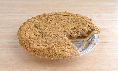 Zijaanzicht van een Nederlandse appeltaart in een aluminiumfolie ovenschaal op een houten tafelblad met een schijfje ontbreekt. Stockfoto