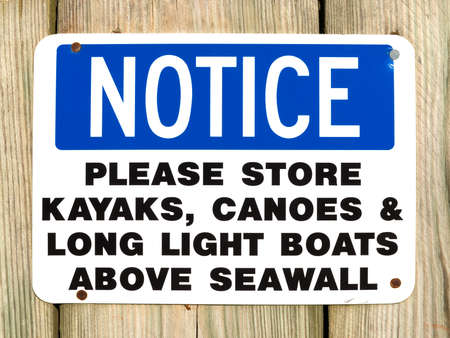treated board: A notice sign to store canoes, kayaks and light boats above a seawall attached to pressure treated boarding. Stock Photo