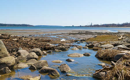 runoff: Wide view of fresh water runoff into Long Cove at Searsport Maine with a working pier in the distance.