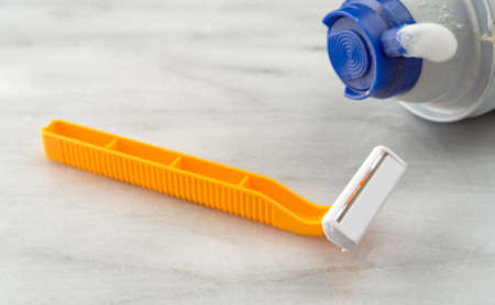 counter top: A generic disposable shaving razor with an empty can of foam on a marble counter top.