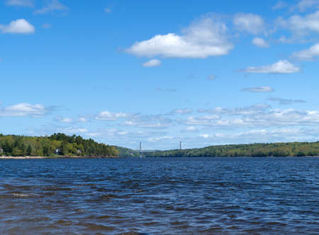 A distant view of the Penobscot Narrows Bridge over the river from Sandy Beach in Stockton Springs, Maine.