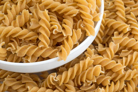 overflowing: A bowl of fusilli whole wheat organic pasta in an overflowing white bowl.