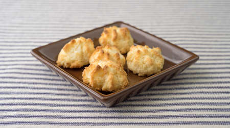 free dish: A serving of sugar free coconut macaroons in a small dish atop a blue striped tablecloth. Stock Photo