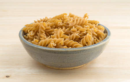 stoneware: An old stoneware bowl filled with fusilli whole wheat organic pasta on a wood table top. Stock Photo
