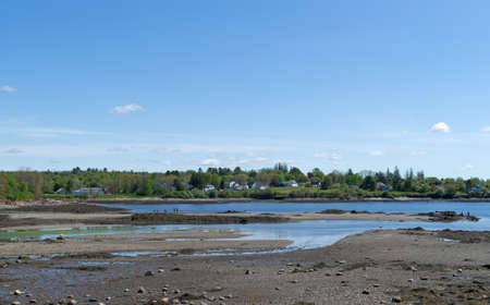 spring tide: Low tide at Searsport, Maine with in the distance people on an above water sandy peninsula on a warm spring morning.